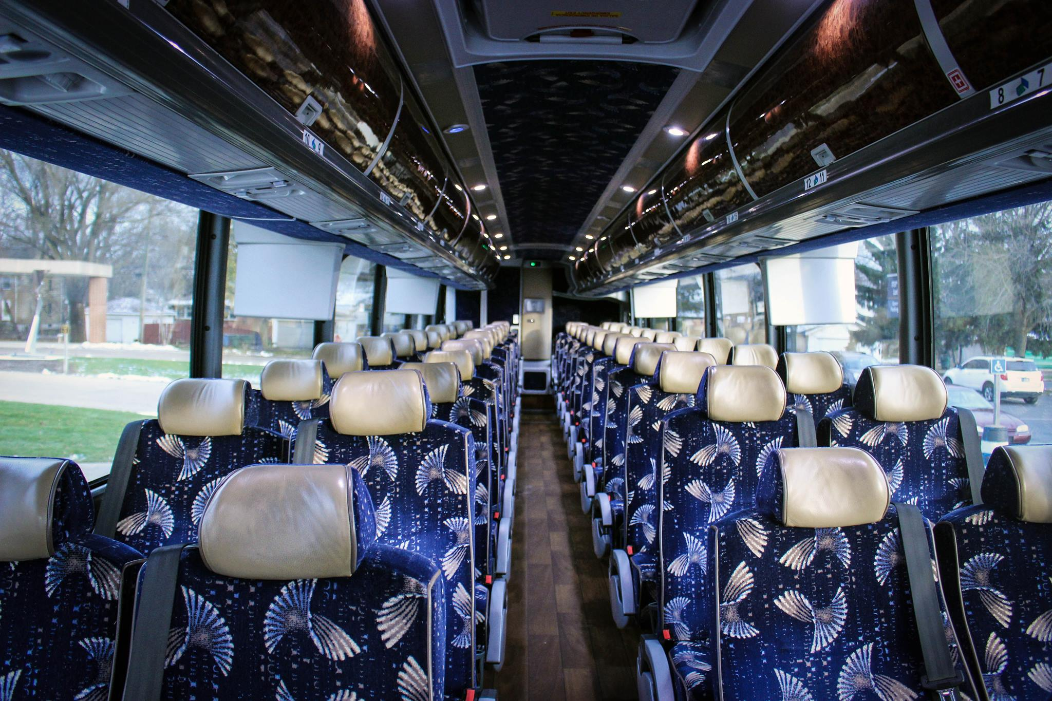 The buses for bringing students and faculty members between campuses have hardwood floors, footrests, televisions, a restroom, overhead storage and adjustable lighting.