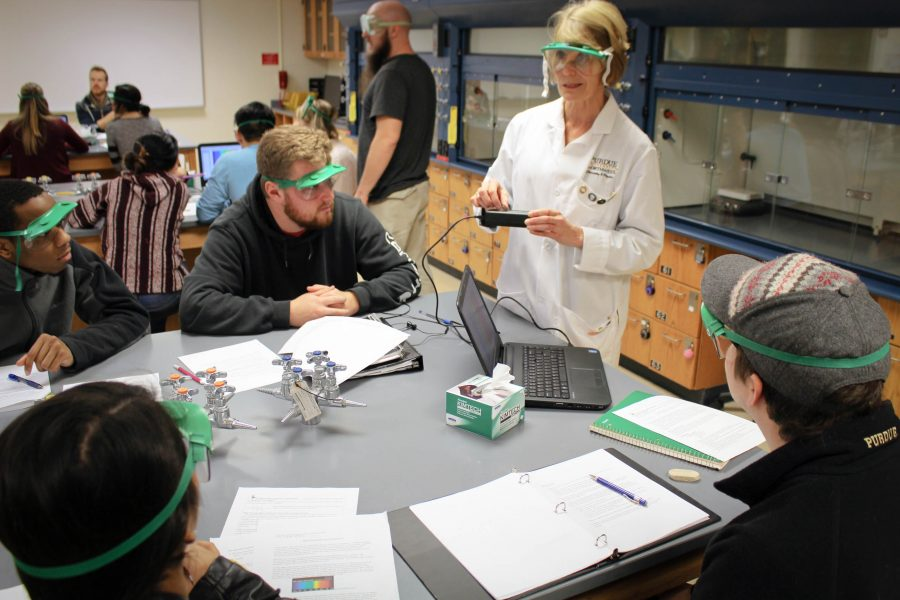 Kathryn Rowberg, associate professor of chemistry, gives a demonstration to her students.