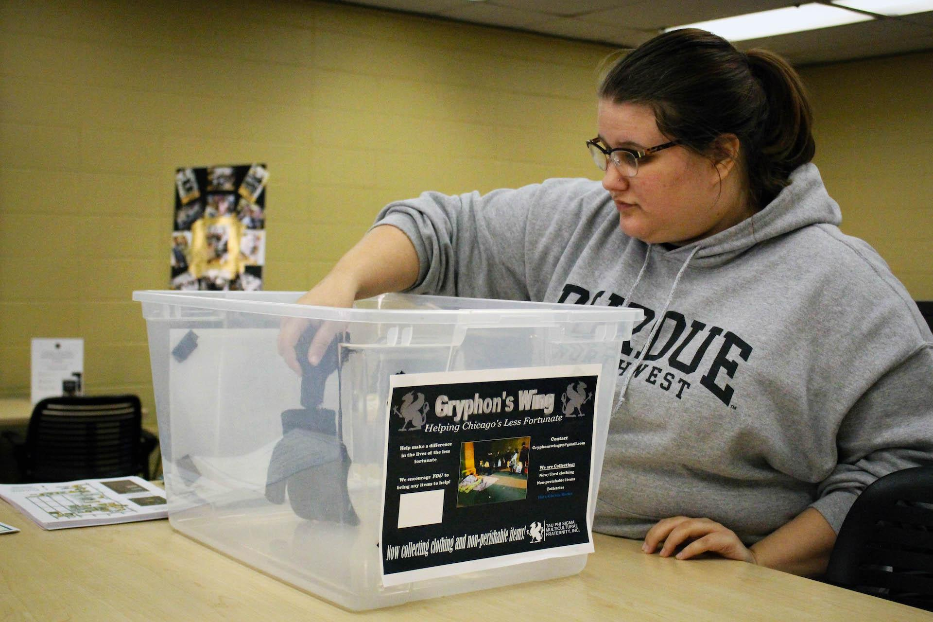 Kathryn Baum, junior communications major, places an item in the donation bin.