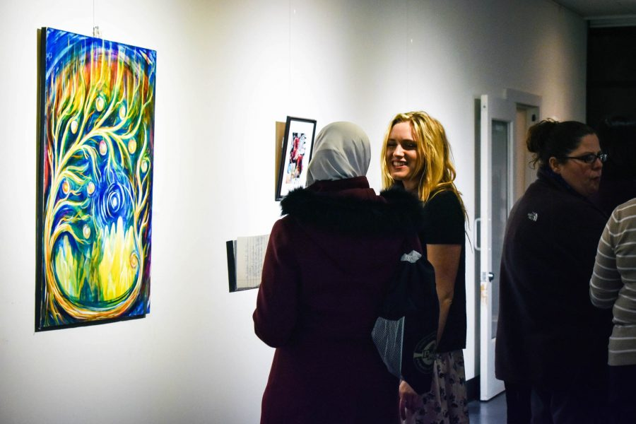 Sara Opat, communication major, speaks to another guest about the gallery.