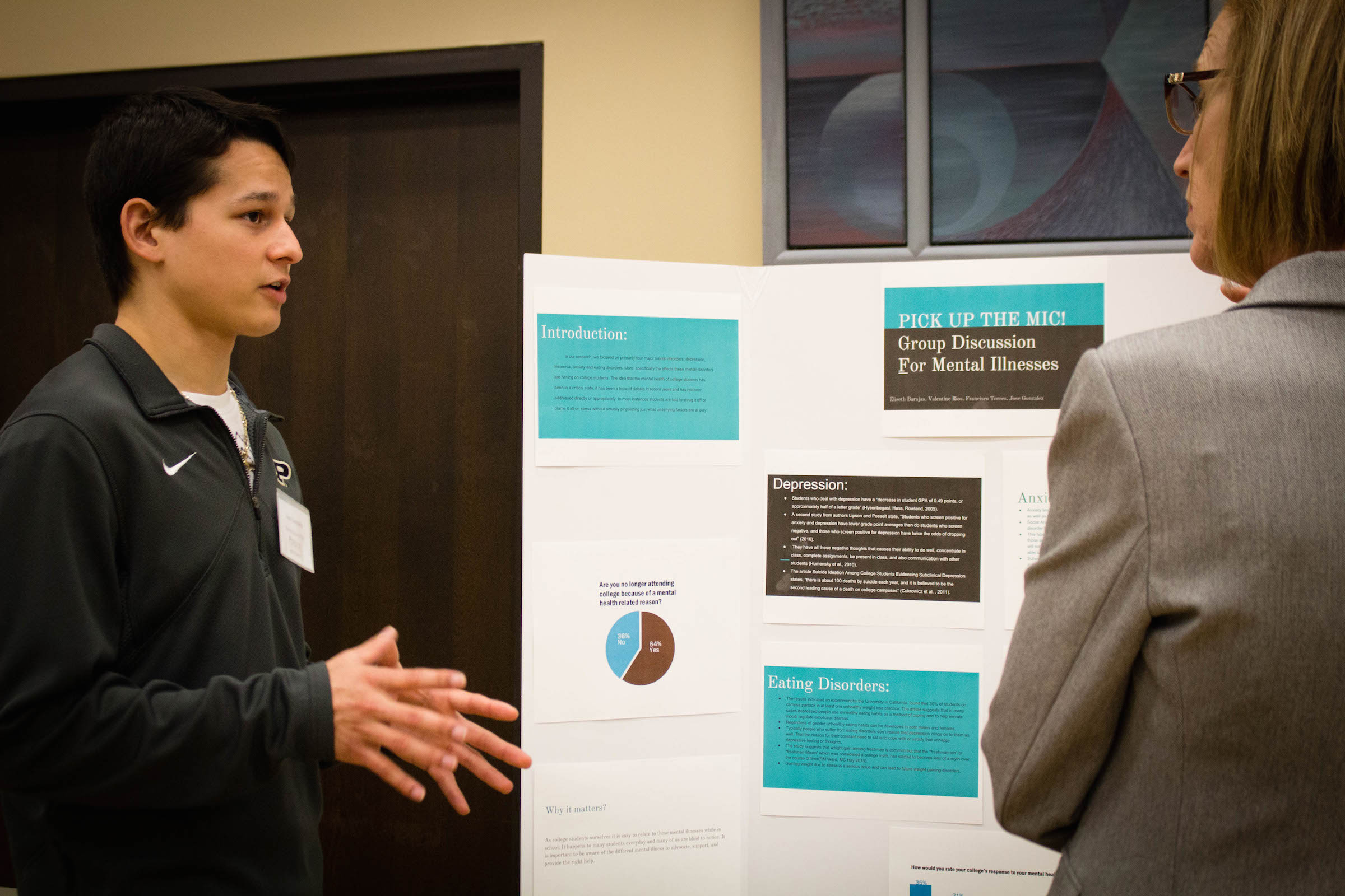 Jose Gonzalez, freshman construction management and accounting major (left), speaks about his presentation during Student Research Day.