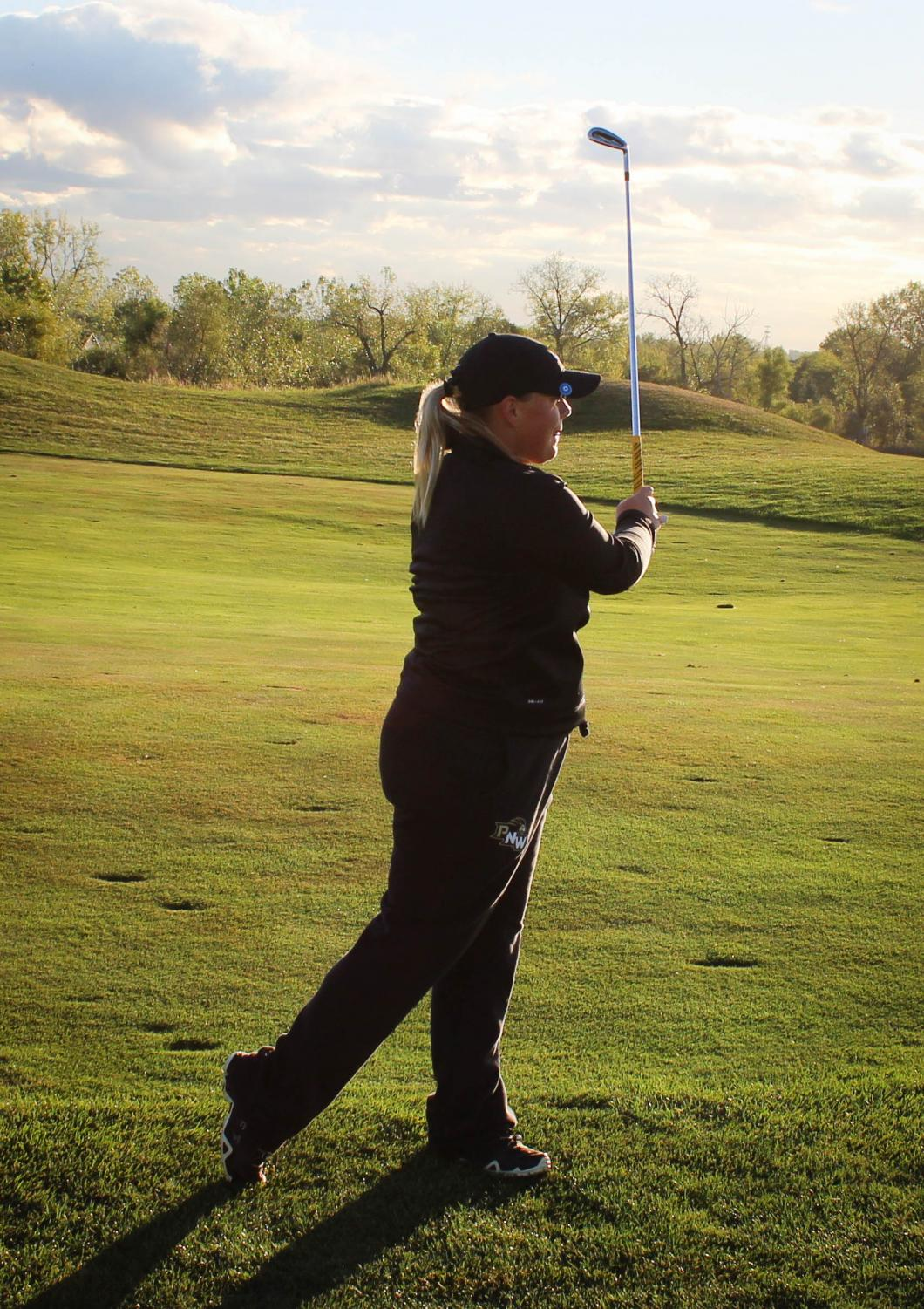 Lauren Bailey, sophomore marketing major, practices her swing for the upcoming invitational.