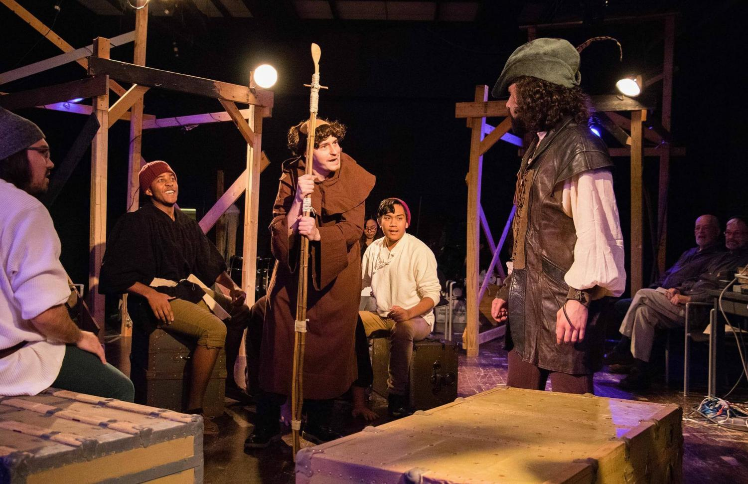 Friar Tuck (front left), played by Jake Johnston, and Robin Hood (right), played by Cristian Galvan, discuss Robin entering the archery tournament. The Merry Men, played by Steven Ulam, Isaac Tolliver, Niko Cabela (from left to right) listen.