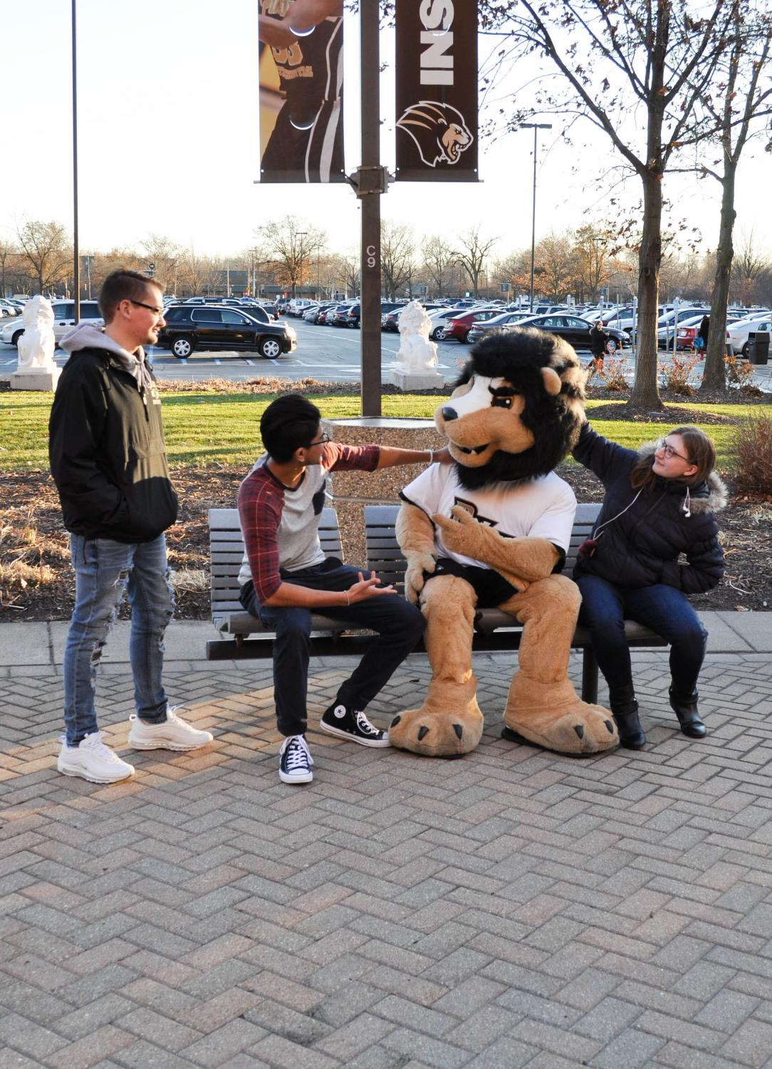 Matthew Kiel (left), freshman engineering major, Ruben Gonzalez (left center), freshman criminal justice major, and Kalina Ziemlo (right), freshman elementary education major hang out with Leo.