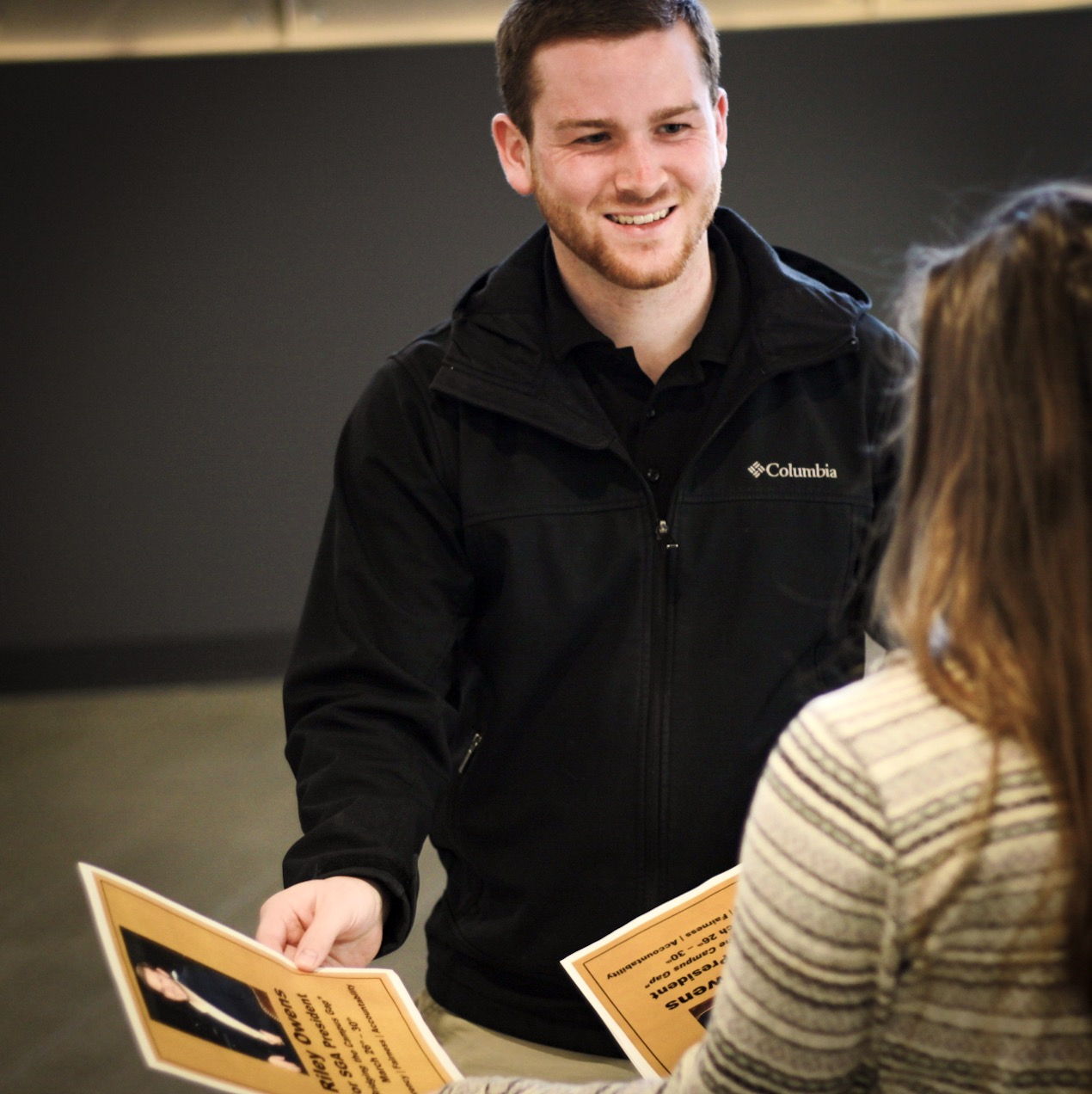 Riley Owens talks to PNW students while passing out his campaign flyers for the SGA presidential race.