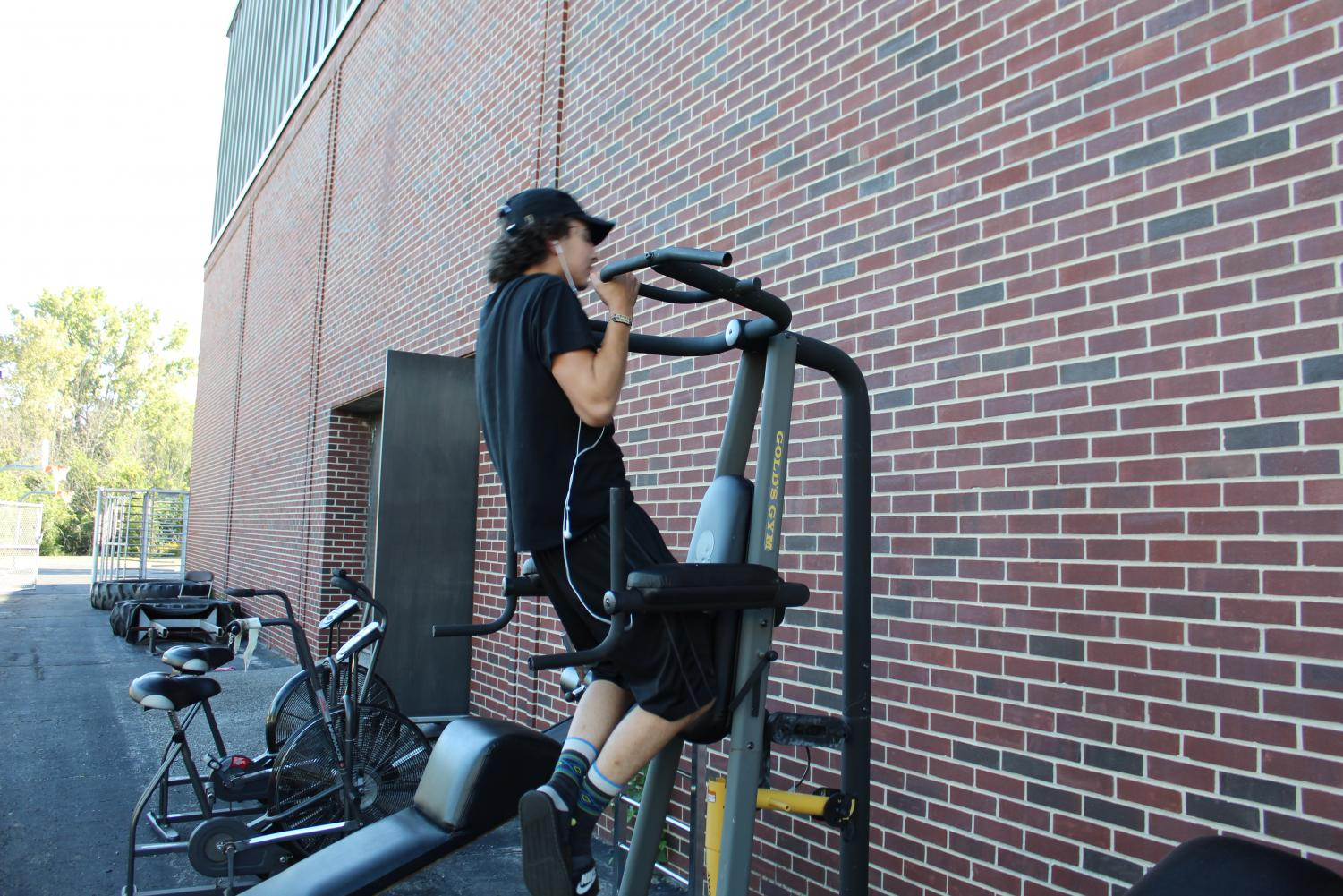 Joshua Perez, Fitness Center employee, works out on the Lion's Cage equipment outside the east side of the Fitness center.