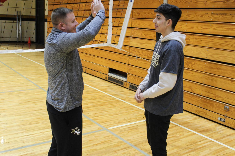 JJ Glavan, men's club volleyball head coach, teaches David Herrera, freshman health studies major, how to set.